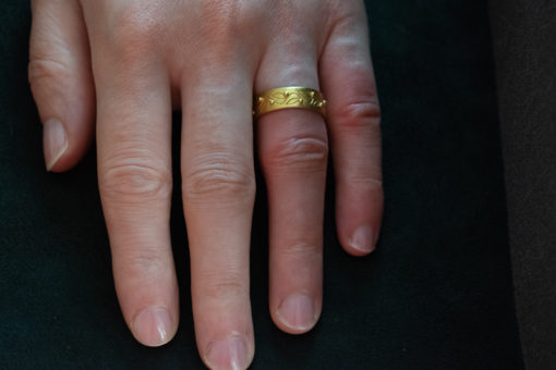 carved 22ct gold ring on finger