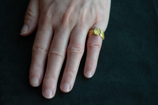 22ct gold hand carved ring with a small pressed flower on top